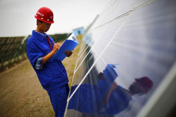 A worker inspects solar panels in Dunhuang, Gansu Province, China, Sept. 15, 2013. REUTERS/Carlos Barria