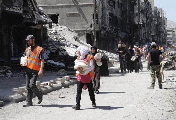 Palestinians from the besieged al-Yarmouk camp receive food aid from UNRWA at the entrance of the camp in Rama street, which is controlled by forces loyal to Syria's President Bashar al-Assad, south of Damascus, April 24, 2014. REUTERS/Rame Alsayed