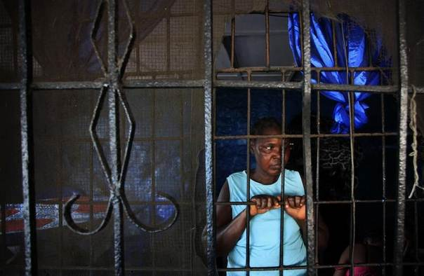 A woman stands at her window at the DuPort Road area, in Monrovia, Liberia January 29, 2013. 2013. REUTERS/Thierry Gouegnon