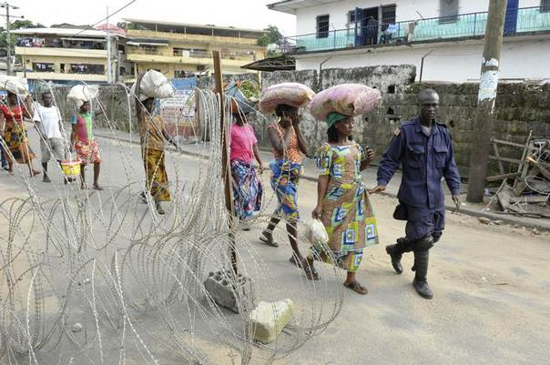 People living outside the Ebola quarantine area of Westpoint walk at a checkpoint while carrying food and essentials for their relatives in quarantine, in Monrovia August 23, 2014.REUTERS/2Tango