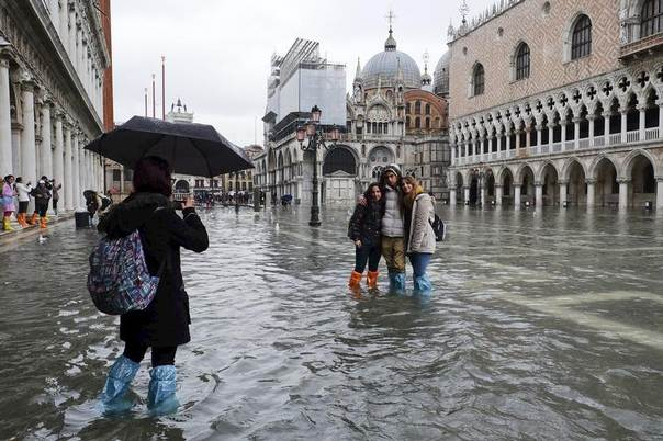 Tourists pose for a photo in a flooded St. Mark's Square, Venice January 31, 2014. REUTERS/Manuel Silvestri