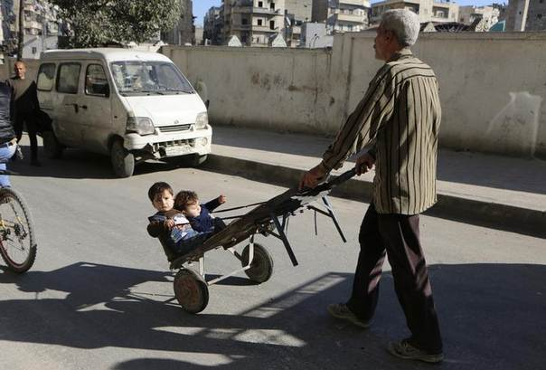 A man wheels children at the Karaj al-Hajez crossing, a passageway separating Aleppo's Bustan al-Qasr, which is under the rebels' control and Al-Masharqa neighbourhood, an area controlled by the regime February 20, 2014. REUTERS/Hosam Katan