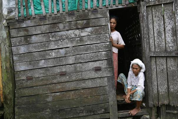 Rohingya Muslim women look out from the front of their home at Aung Mingalar quarter in Sittwe, Myanmar, August 13, 2013. REUTERS/Soe Zeya Tun