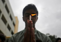 A schoolboy holds a candle as he prays to pay tribute to Hindu pilgrims