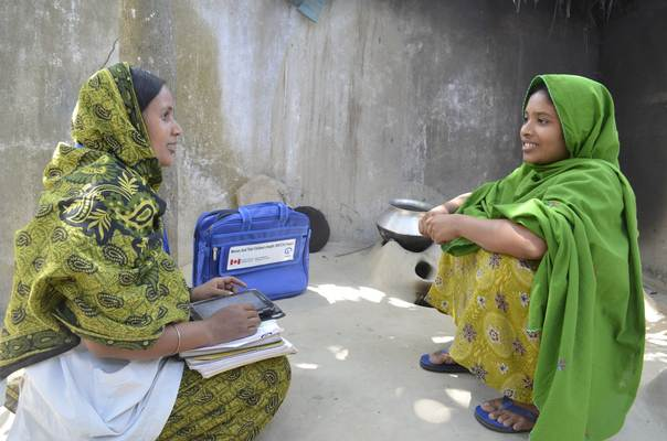 Health worker Shahanaj Parvin using a computer tablet during a consultation with her patient . Photo credit: Plan International/Mahedul Islam