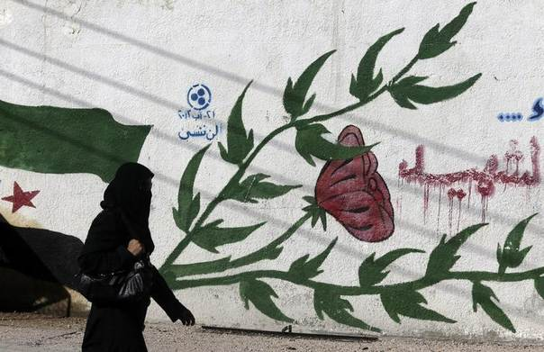 A woman walks past graffiti on a wall in Erbeen, in the eastern Ghouta suburb of Damascus August 21, 2014. REUTERS/Bassam Khabieh