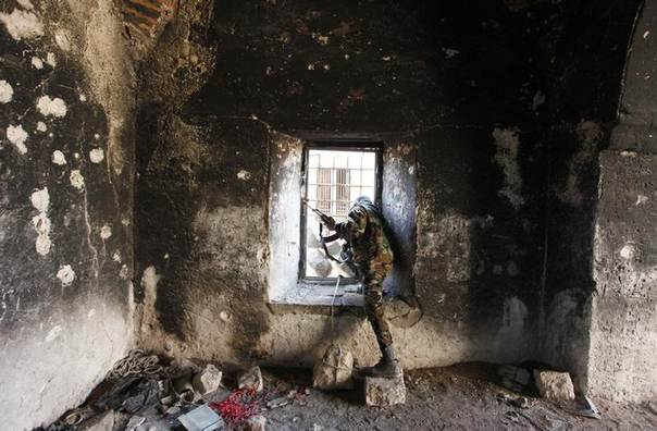 A Free Syrian Army fighter looks through a window of a damaged house in Old Aleppo, December 15, 2013. REUTERS/Molhem Baraka