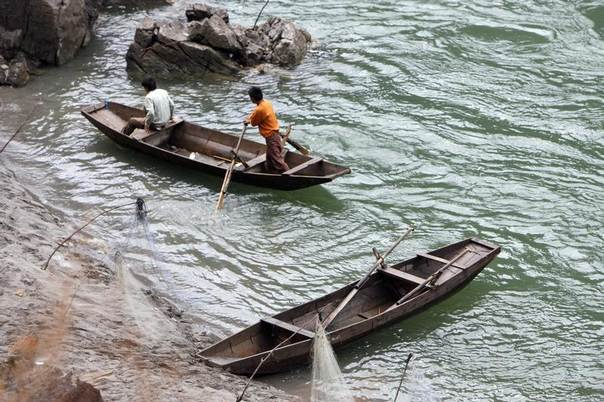 Fishermen sail their boats to the bank of the Nu River, also known as the Salween River, near Lushui in southwest China's Yunnan province March 3, 2007. REUTERS/Nir Elias
