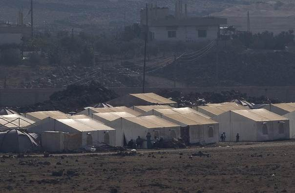 Syrian refugees sit outside their tents at Al Rafid village, Quneitra, Syria, close to the border with the Israeli-occupied Golan Heights. Picture August 29, 2014.  REUTERS/Ronen Zvulun