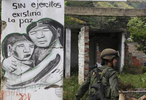 A Colombian police officer walks by a mural that reads