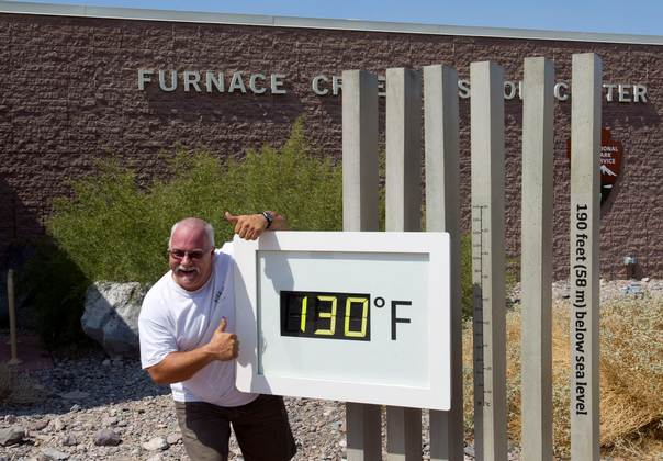 Craig Blanchard, a Park Service employee, poses in front of an unofficial temperature gauge at the Furnace Creek Visitor Center in Death Valley National Park in California on June 29, 2013. REUTERS/Steve Marcus