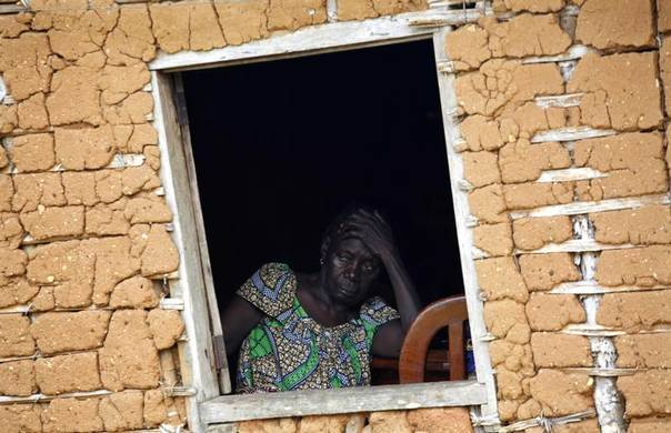 A woman stares out of the window of her mud hut in the village of Farbe, near the site of one of the main seedlings nurseries of the Herakles palm oil farm plantation project in Cameroon, June 8, 2012. REUTERS/Emmanuel Braun