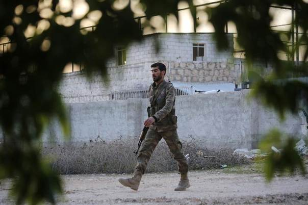 A rebel fighter carries his weapon as he walks near the 80th Brigade base in Aleppo April 1, 2014. Picture taken April 1, 2014. REUTERS/Hamid Khatib