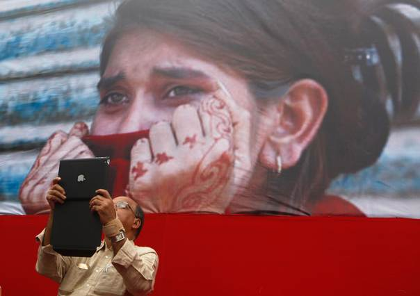 In a 2012 file photo, a member of the Communist Party of India-Marxist (CPI-M) uses an iPad to take pictures of a protest in Kolkata against attacks on women. REUTERS/Rupak De Chowdhuri