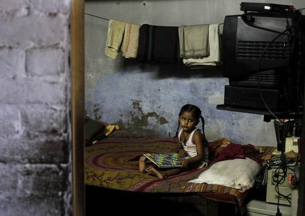 A girl plays a game inside her home at a slum in New Delhi September 23, 2013. REUTERS/Anindito Mukherjee