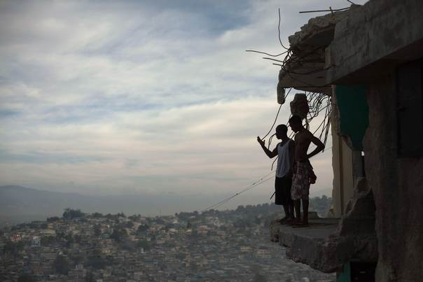 In a file photo, Orich Florestal (L), 24 and Rosemond Altidon, 22, stand on the edge of their partially destroyed apartment of Port-au-Prince on Jan. 9, 2011, a year after the earthquake that wrecked much of the capital. REUTERS/Allison Shelley