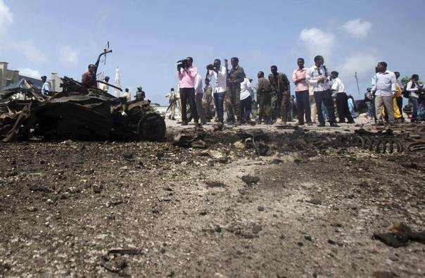 Journalists take pictures of the wreckage after a suicide car explosion near the Somali parliament building in Mogadishu July 5, 2014. REUTERS/Ismail Taxta