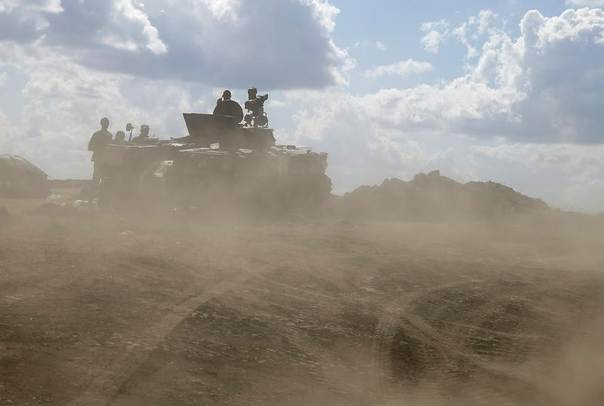 Ukrainian army servicemen around an armoured vehicle are seen through dust raised by passing vehicles near Debaltseve, Donetsk region, August 29, 2014. REUTERS/Gleb Garanich