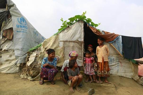 A family sits in front of their temporary shelter at a Rohingya refugee camp as Myanmar's government embarks on a national census, in Sittwe April 2, 2014. REUTERS/Soe Zeya Tun