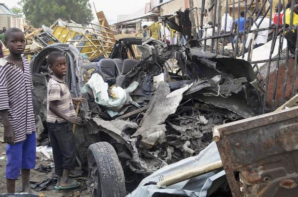 Two boys stand near the charred chassis of a vehicle after a bomb attack near a busy market area in Ajilari-Gomari near the city's airport, in Maiduguri March 2, 2014 REUTERS/Stringer