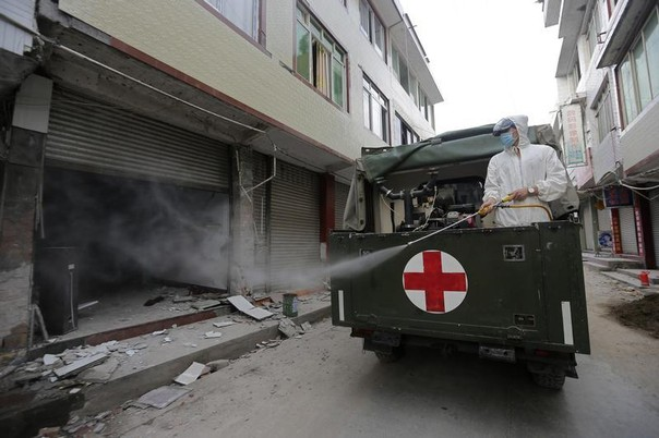 A worker sterilizes a house damaged in an earthquake