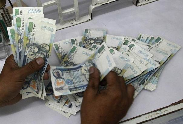 In this 2012 file photo, a worker counts one thousand pesos bills inside a money changer in Manila REUTERS/Romeo Ranoco