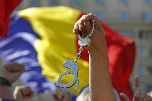 In this 2012 file photo, a protester holds a pair of handcuffs during an anti-presidential rally in front of Romania's Constitutional Court in Bucharest REUTERS/Bogdan Cristel
