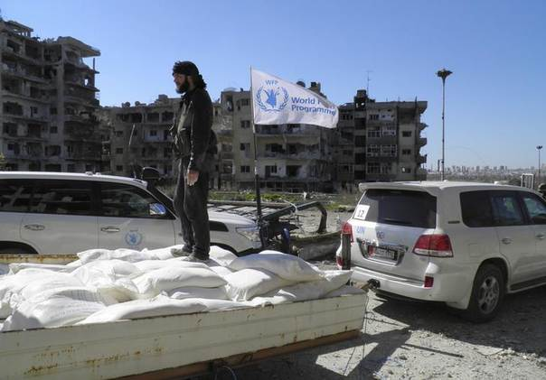 A Free Syrian Army fighter stands atop bags of U.N. humanitarian aid at a besieged area of Homs February 12, 2014 REUTERS/Thaer Al Khalidiya