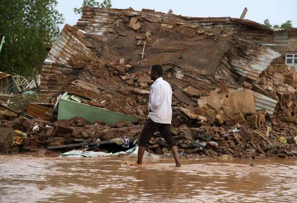 A man walks past a house destroyed by flood waters in Salhaa, Omdurman, after heavy rains led Khartoum state to declare a high state of alert. Picture July 30, 2014. REUTERS/Mohamed Nureldin Abdallah