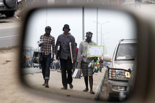 Men reflected in the side mirror of a car, hawks their wares in traffic along a road in Ajah district in Nigeria's commercial capital Lagos July 5, 2014. REUTERS/Akintunde Akinleye