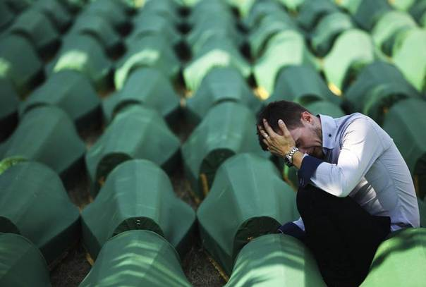 A Bosnian Muslim man sits and cries near the coffin of his relative at Memorial Center in Potocari before a mass burial, near Srebrenica July 11, 2012. REUTERS/Dado Ruvic