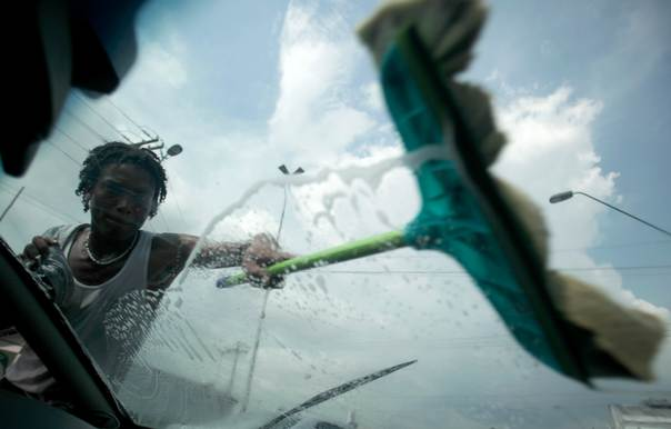 In a 2011 file photo, a Haitian man cleans a car window in Manaus, Brazil. Since the January 12, 2010 earthquake struck Haiti, hundreds of Haitians have been migrating to Brazil via Peru and Ecuador. Most work in construction and in factories, earning little more than the minimum wage of $300 monthly, leaving them little or no money to send home to family in Haiti, according to the Association of Haitian Workers in Manaus. REUTERS/Ricardo Moraes