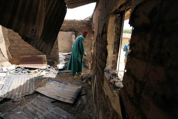 Pius Nna, the village head of Angwan Gata, walks through one of the rooms destroyed when gunmen attacked his village in Kaura local government Kaduna State, Nigeria, March 19, 2014. REUTERS/Afolabi Sotunde