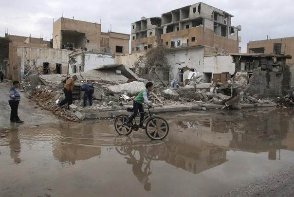 A boy rides a bicycle past damage at a site hit by what activists say was a Scud missile from forces loyal to Syria's President Bashar al-Assad, in Raqqa, eastern Syria, November 29, 2013. REUTERS/Nour Fourat