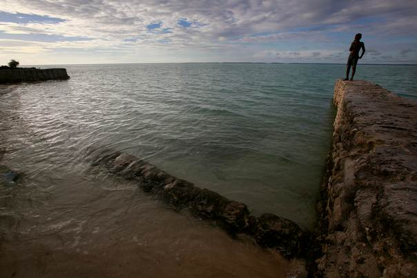 A boy stands on top of a sea wall near the village of Tangintebu on South Tarawa in the central Pacific island nation of Kiribati on May 26, 2013. REUTERS/David Gray