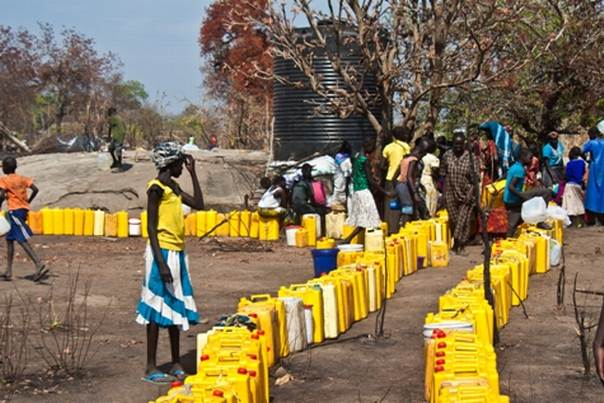 Jerry cans lined up as women queue for water, Uganda