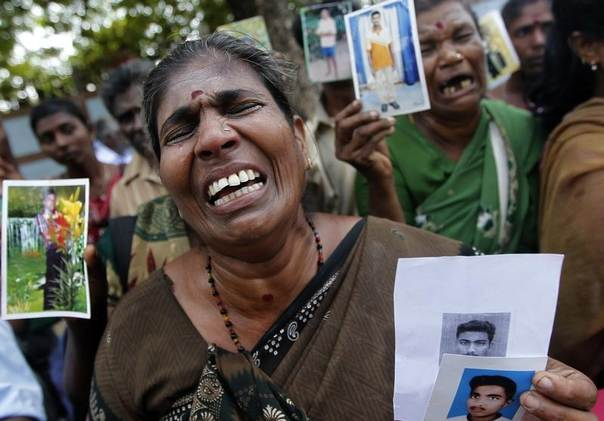 A Tamil woman cries as she holds up an image of her disappeared family member during Sri Lanks's civil war, August 27, 2013.  REUTERS/Dinuka Liyanawatte