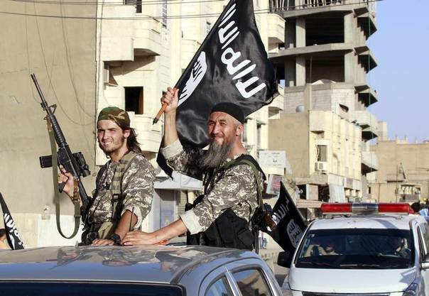 Militant Islamist fighters wave flags as they take part in a military parade along the streets of Syria's northern Raqqa province June 30, 2014. REUTERS/Stringer