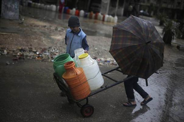 Boys push a cart with water containers during rainy weather in the Duma neighbourhood of Damascus May 8, 2014. REUTERS/Bassam Khabieh