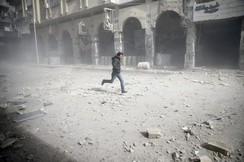 A man is seen running after an air raid in the besieged town of Douma in eastern Ghouta in Damascus