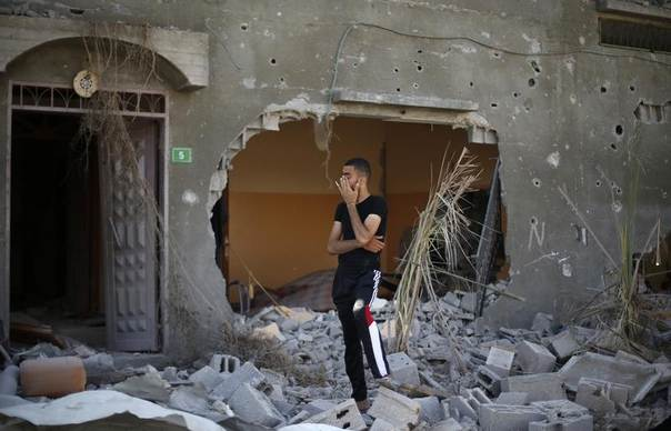 A Palestinian man stands outside his badly damaged house in Beit Hanoun town, which witnesses said was heavily hit by Israeli shelling and air strikes during an Israeli offensive, in the northern Gaza Strip, August 1, 2014. REUTERS/Suhaib Salem