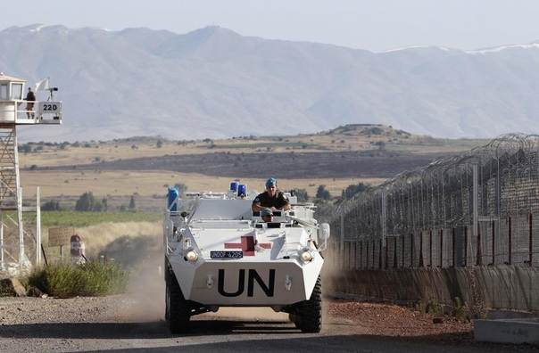 United Nations peacekeeping soldiers from Austria drive past an observation tower near the Quneitra border crossing between Israel and Syria, on Israeli-occupied Golan Heights June 12, 2013.  REUTERS/Ammar Awad