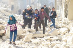 People and a civil defence personnel carry children after an airstrike on Idlib city, Syria