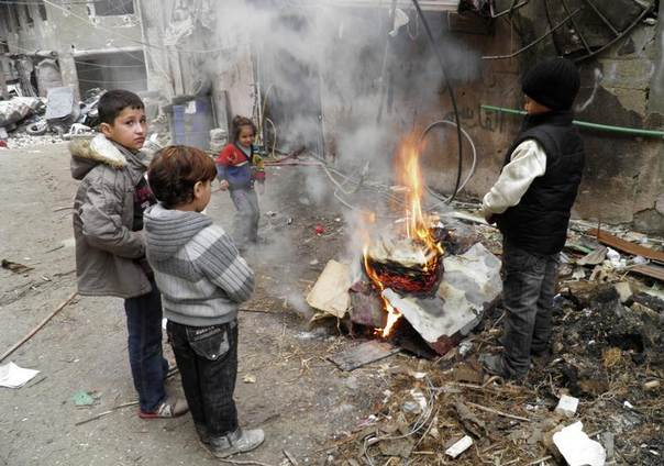 Children warm themselves around a fire in the besieged area of Homs, Syria, January 27, 2014. REUTERS/Thaer Al Khalidiya