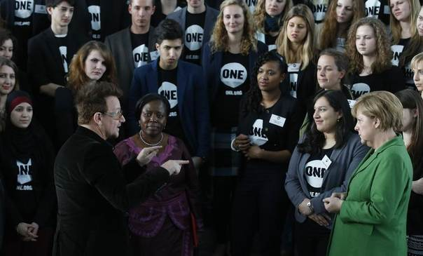 Bono, lead singer of the band U2 and ONE organisation co-founder (2nd L) and German Chancellor Angela Merkel (R) pose with youth representatives of the organisation ONE against human poverty, in Berlin April 8, 2013. REUTERS/Tobias Schwarz