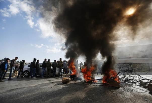 Tyres set on fire by Palestinian youths block a road during a protest in the Jalazoun refugee camp near the West Bank city of Ramallah, January 9, 2014.  REUTERS/Mohamad Torokman