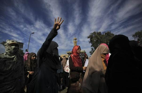 Female students of Al-Azhar University, supporters of the Muslim Brotherhood and ousted Egyptian President Mohamed Mursi, shout slogans against the military and interior ministry while gesturing with four fingers after last night's clashes as they block Moustafa Al Nahas street in front of Al-Azhar University Campus at Cairo's Nasr City district, November 21, 2013. REUTERS/Amr Abdallah Dalsh