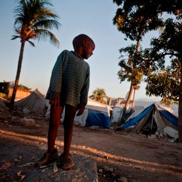A scene shows  a young standing in front of a tightly packed camp on a hillside in Port au Prince, Haiti on the 13th January, 2013. Three years ago a powerful earthquake claimed the lives of over 200,000 people and displaced thousands more - over 350,00 are still living in camps like this despite a multi billion pound aid effort. Photo: Kate Holt/CARE