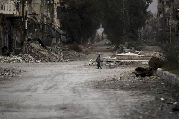A child walks along a damaged street covered with debris in Deir al-Zor, eastern Syria, February 3, 2014. EUTERS/Khalil Ashawi