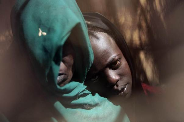 Displaced Sudanese Fatna Adam Hamed (R), 11, who was raped by armed men, leans on her mother's shoulder in a camp in Nyala, southern Darfur March 18, 2009. REUTERS/Zohra Bensemra